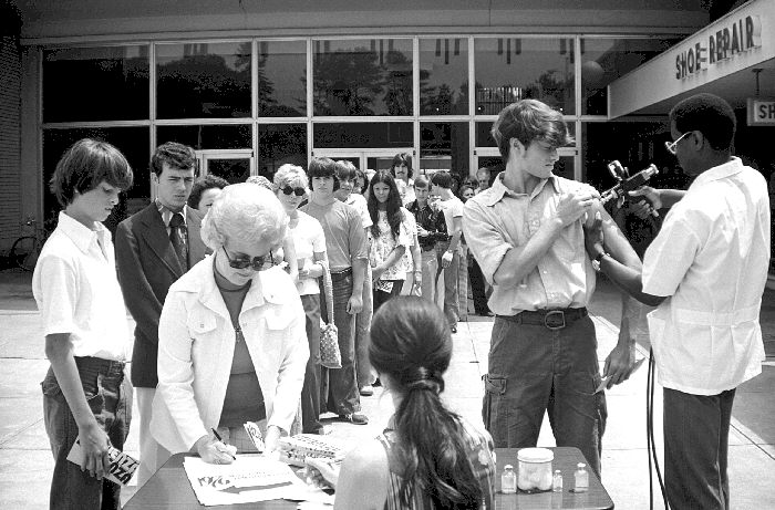 A black and white photo showing a line of people in waiting to receive the 1976 swine flu vaccine.