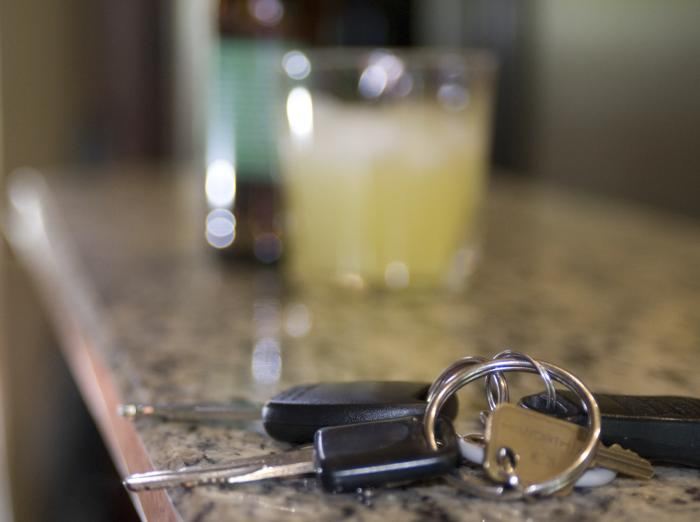 This image depicts a symbolic scenario including a bottle of beer and mixed drink in the background, and in the extreme foreground, a set of car keys had been laid to rest on what appeared to be a bar's granite countertop.