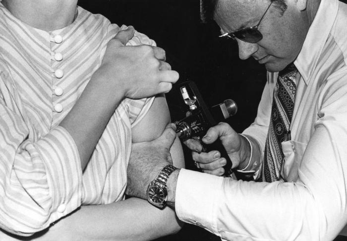 A black and white photo showing a woman receiving the swine flu vaccine from a man using a jet gun injector.